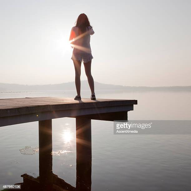 Italian teenage girl stands on wooden pier above lake