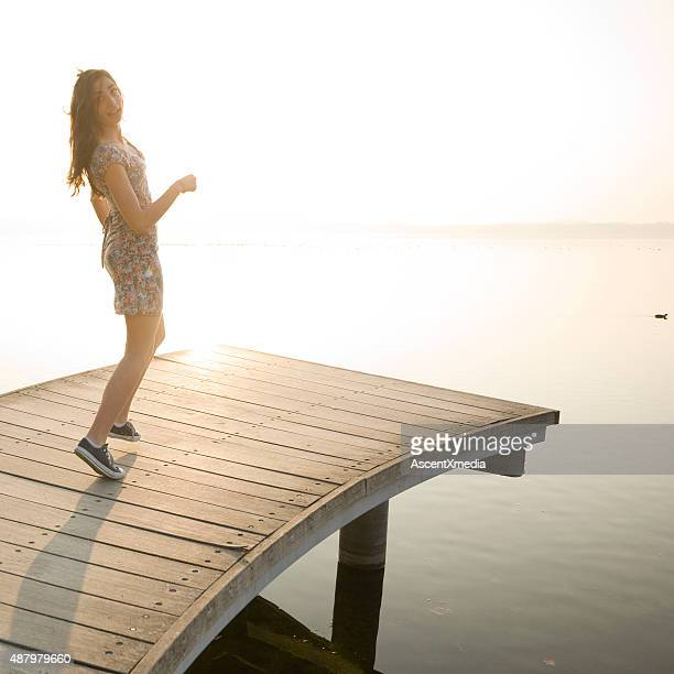 Italian teenage girl walks on wooden pier above lake