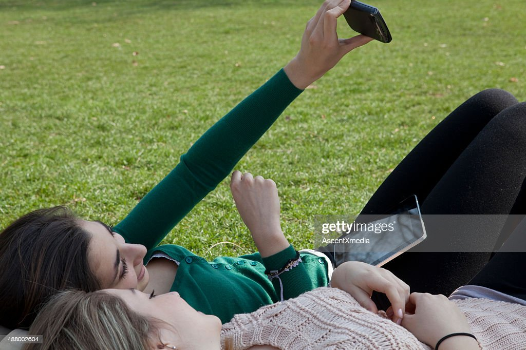 Italian Teenage Girls Lie On Grass Look At Cell Phone Stock Photo
