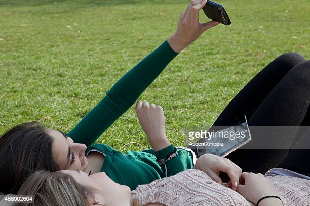 Italian teenage girls lie on grass, look at cell phone