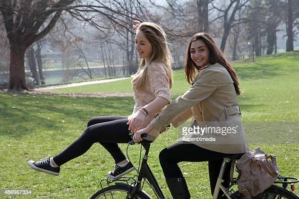 Italian teenage girls ride bicycle handlebars