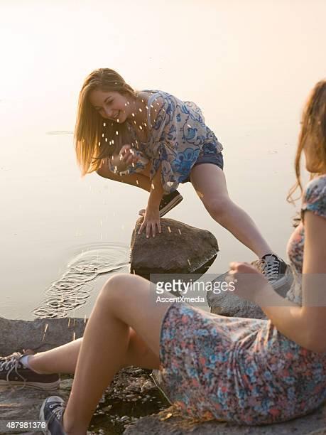 Italian teenage girls splash each other by lakeshore