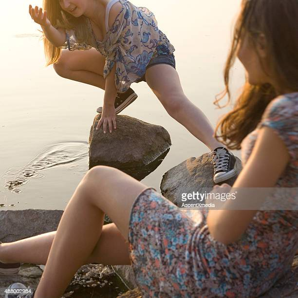 Italian teenage girls splash each other, lakeshore