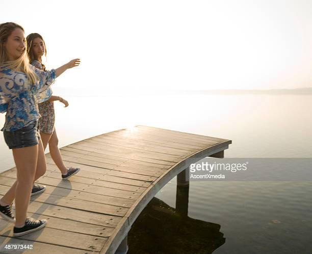 Italian teenage girls walk along wooden pier by lake