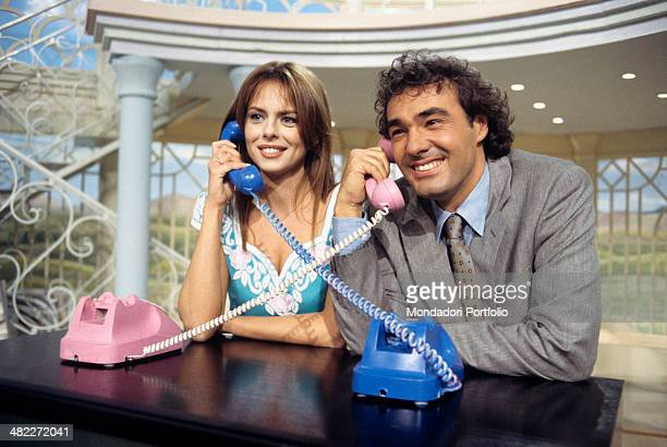 Italian television presenter Paola Perego and Italian presenter and journalist Massimo Giletti smiling on the telephone during the TV broadcast...