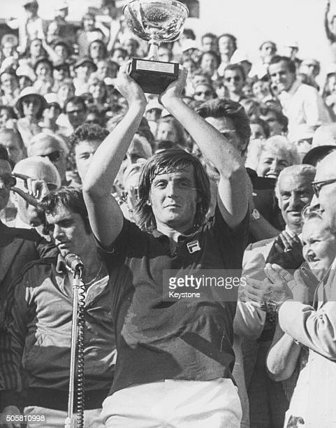 Italian tennis player Adriano Panatta holding his trophy in the air after winning the French Open Tennis Championships at Roland Garros Paris 1976