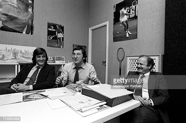 Italian tennis player Adriano Panatta smiling sitting in front of a desk in company of two men 1970s