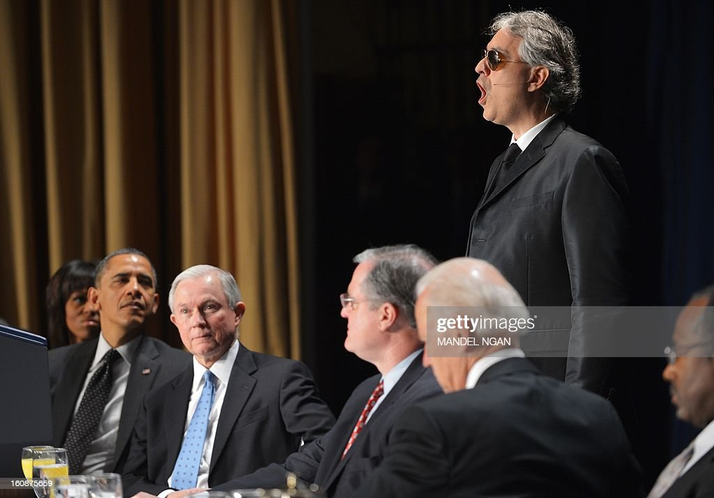 Italian tenor Andrea Bocelli performs during the National Prayer Breakfast as First Lady Michelle Obama (L), US President Barack Obama (2nd L) and Senator Jeff Sessions (3rd L), R-AL, watch on February 7, 2013 at a hotel in Washington, DC. AFP PHOTO/Mandel NGAN