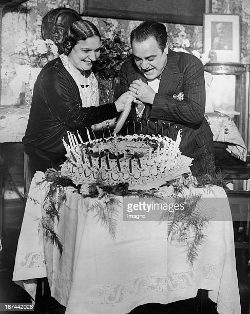 Italian tenor Beniamino Gigli celebrates his 38th Birthday with his wife The couple cut the cake together New York Photograph 1928 Der italienische...