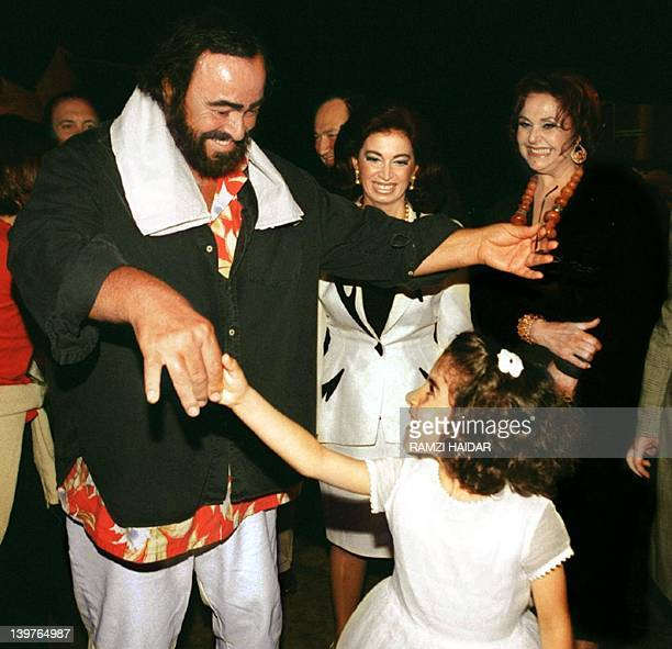 Italian Tenor Luciano Pavarotti dances with a Lebanese girl upon his arrival at Beirut airport 10 June 1999 while Nazik Hariri wife of former prime...