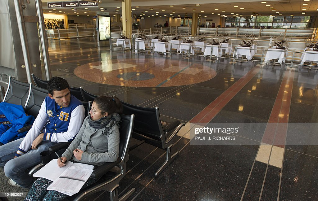Italian tourists Patrizio D'Emido (L) and his girlfriend Joelle Carota (R) sit in the closed Ronald Reagan National Airport stranded between flights with a handful of other travelers as Hurricane Sandy blows through Washington, DC, October 29, 2012. Carota is from Italy and a foreign exchange student at Nazereth College in Rochester, NY, and her home school THE University Gabriele D'Annunzio in Pescura, Italy. Her boyfriend came to visit on a budget and the two didn't want to pay the money for an airport hotel that seemed to have inflated their prices. They have been eating from the only open place at the airport, a donut shop. They plan on sleeping at the airport until the storm passes and air travel resumes. AFP PHOTO/Paul J. Richards