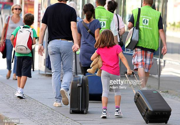 Italian tourists pull rolling suitcases to their hotel on August 15 2012 in Berlin Germany In 2010 nine million tourists visited the German capital...