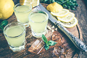 Traditional homemade lemon liqueur limoncello and fresh citrus on the old wooden board. Italian traditional liqueur limoncello with lemon. Italian alcoholic beverage. Selective focus and toned image.