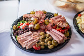 Platter containing many cold cuts, pepers, olives, and other vegetables.
