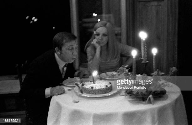 Italian TV and radio presenter Mike Bongiorno blowing out the candle of his fortythird birthday cake His partner the Italian journalist and art...