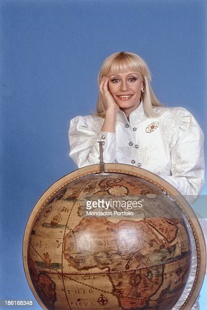 Italian TV host actress singer and showgirl Raffaella Carrà leaning on a globe in the TV show Raffaella Carrà Show Italy 1988