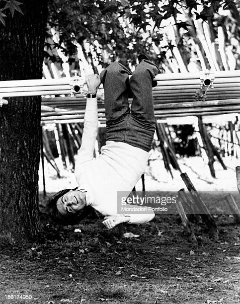 Italian TV host and producer Paolo Limiti hanging on the pole of a play structure for children Milan 1970s