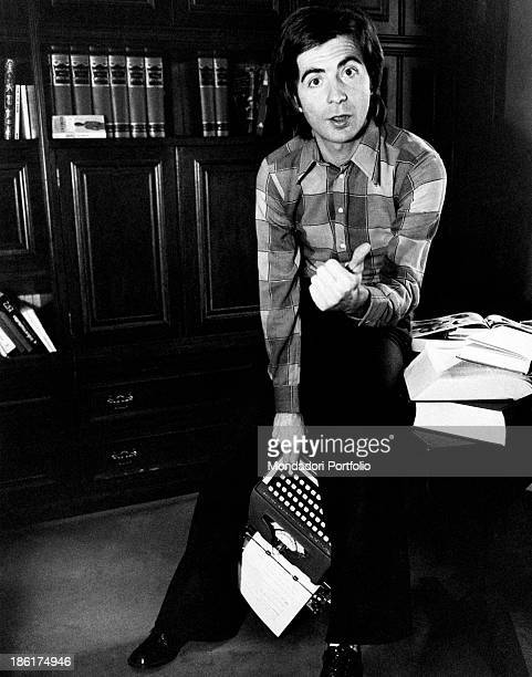 Italian TV host and producer Paolo Limiti posing holding a typewriter Milan 1970s