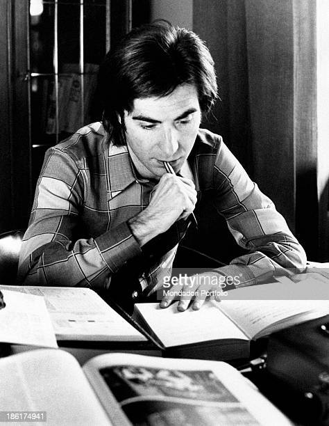 Italian TV host and producer Paolo Limiti reading seated at the desk with a pen in his mouth Milan 1970s