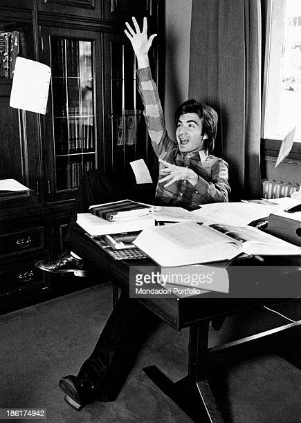 Italian TV host and producer Paolo Limiti smiling and raising his arm seated at the desk Milan 1970s