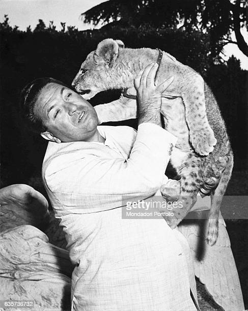 Italian TV host Angelo Lombardi holding a lion cub in the TV show L'amico degli animali 1960