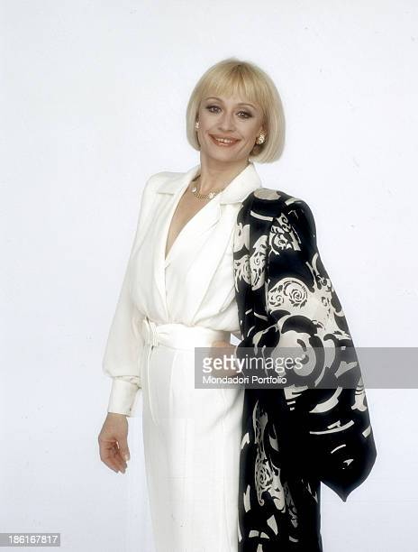 Italian TV presenter actress singer and showgirl Raffaella Carrà wearing a white evening dress trimmed with a stole on her left shoulder 1989