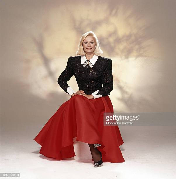 Italian TV presenter actress singer and showgirl Raffaella Carrà wearing a long red skirt and a black lace top designed by Italian fashion designer...