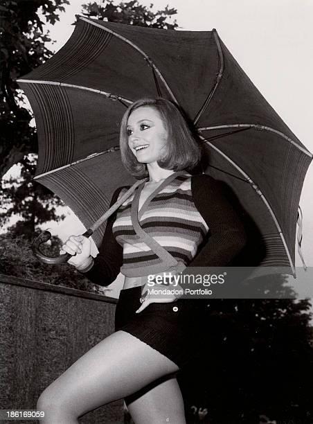 Italian TV presenter actress singer and showgirl Raffaella Carrà walking under an umbrella Italy 1970s