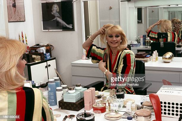 Italian TV presenter actress singer and showgirl Raffaella Carrà combing herself in her dressing room 1983