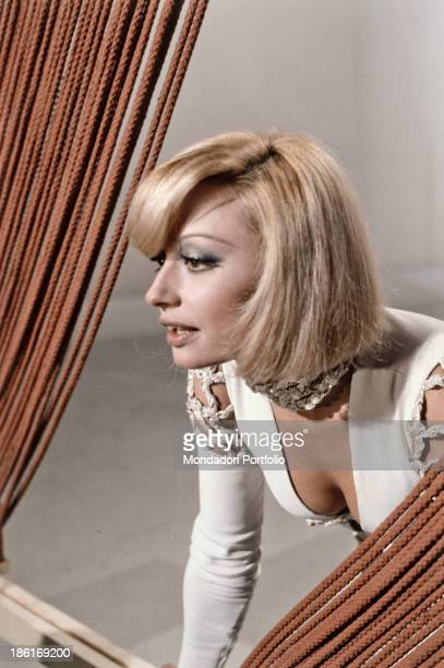 Italian TV presenter actress singer and showgirl Raffaella Carrà leaning on a wooden board in the TV music show Canzonissima Italy 1974