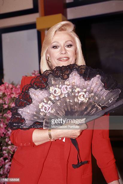 Italian TV presenter actress singer and showgirl Raffella Carrà holding a fan in her right hand The presenter is shooting the TV show La grande festa...
