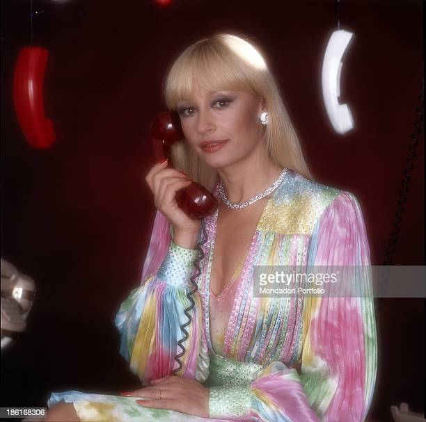 Italian TV presenter actress singer and showgirl Raffella Carrà bringing a receiver near to her right ear in the studios of the TV show Pronto...