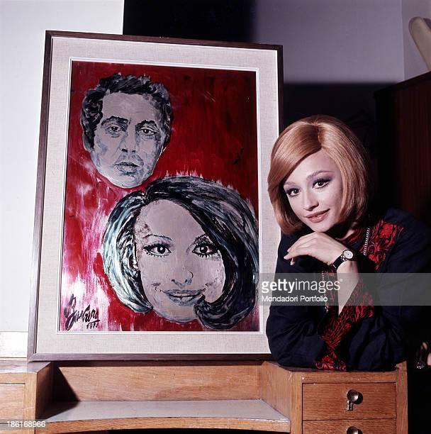 Italian TV presenter actress singer and showgirl Raffella Carrà posing beside a painting portraying herself and Italian radio presenter and director...
