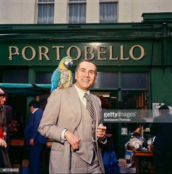 Italian TV presenter Enzo Tortora posing smiling with a parrot on his shoulder in Portobello Road London 1977