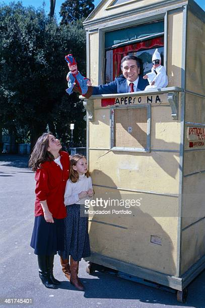 Italian TV presenter Enzo Tortora smiling playing the role of a puppeteer beside his daughters Gaia and Silvia 1978