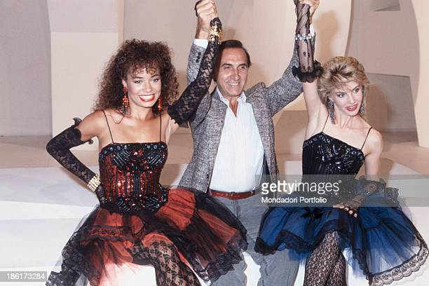 Italian TV presenter Pippo Baudo raising the arms of Italian showgirl and dancer Lorella Cuccarini and American actress and dancer Galyn Gorg in the...