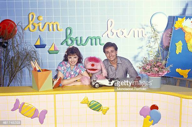 Italian TV presenters Paolo Bonolis and Manuela Blanchard posing smiling with the puppet Uan in the TV studio of the children broadcast Bim Bum Bam...