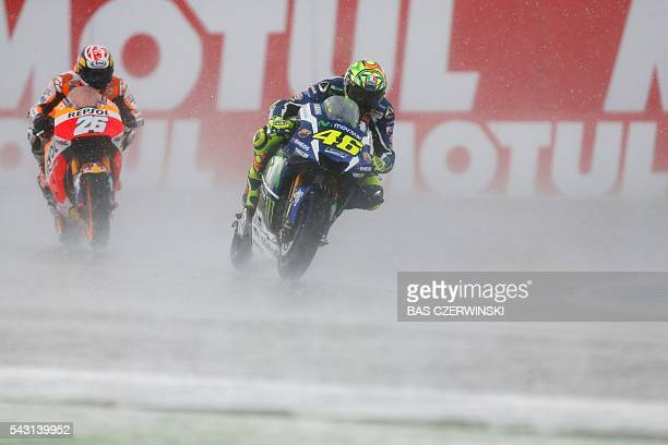 Italian Valentino Rossi on his Yamaha and Spanish Dani Pedrosa on his Honda compete during the MotoGP for the Dutch Motorcycling Grand Prix on June...