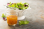 Italian vinaigrette dressing in a mason jar with fresh vegetables on the table