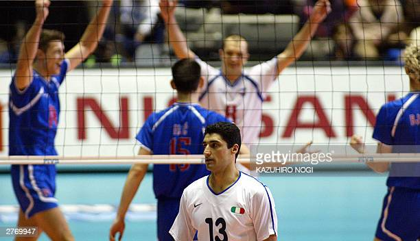 Italian volleyball team captain Andrea Giani leaves a volley court while players of Serbia Montenegro are celebrating their victory over Italy at the...