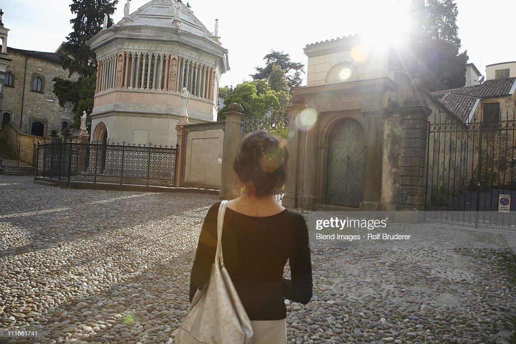 Italian woman standing near gates of building : Stock Photo