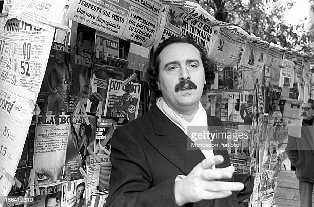Italian writer and poet Giuseppe Conte gesticulating in front of a newsstand Italy 1980s