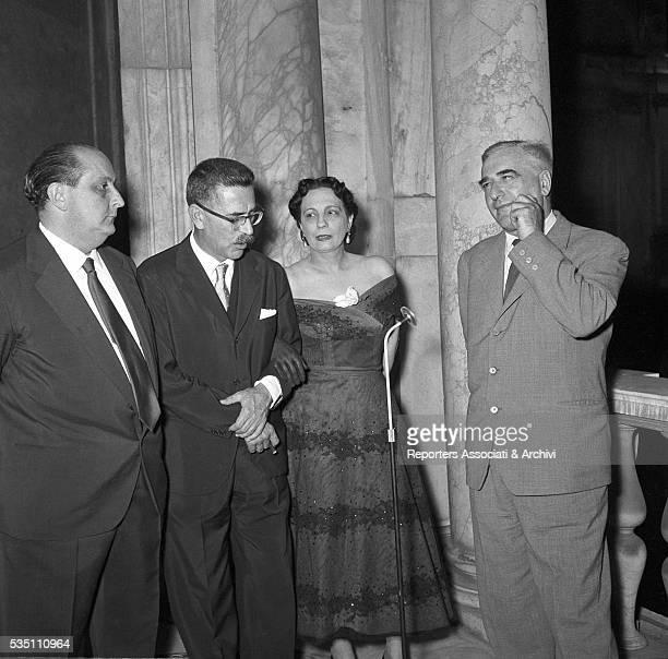 Italian writer and winner of the Strega Prize Giovanni Comisso beside Italian writer and director Mario Soldati arm in arm with Italian writer Maria...