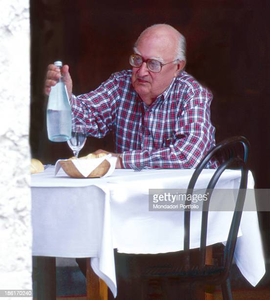 Italian writer Andrea Camilleri sitting at the table with a bottle in the hand Mantova 1992