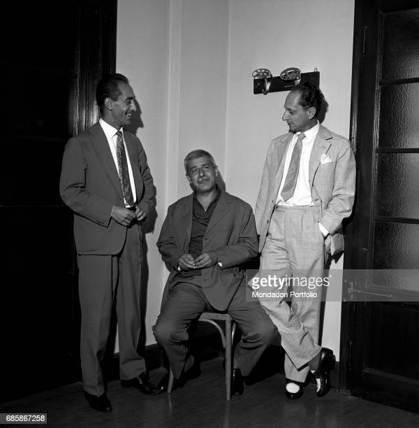 Italian writer Elio Vittorini sitting in the middle of the picture chatting with two friends On his right is recognized Italo Calvino italian writer...
