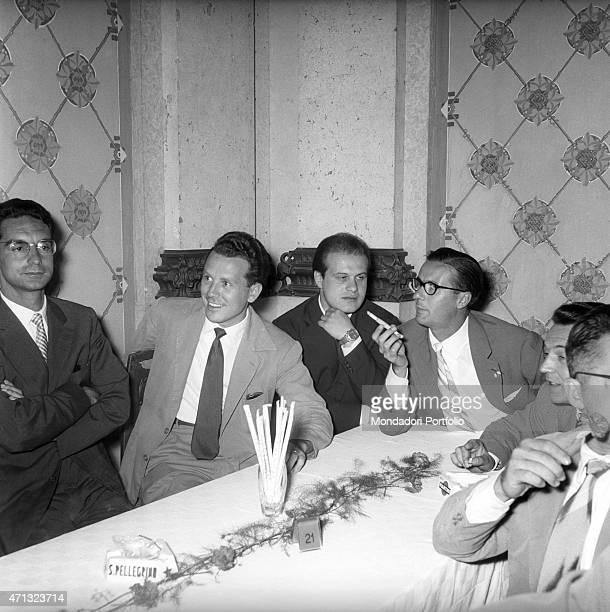 Italian writer Italo Calvino sitting at the table with some other writers at the Incontri Letterari former San Pellegrino Awards San Pellegrino Terme...