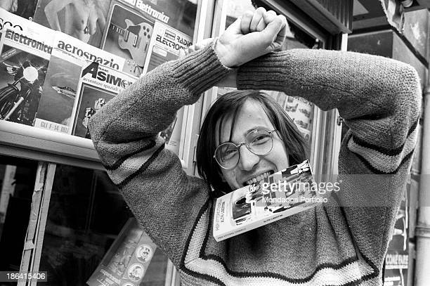 Italian writer Pier Vittorio Tondelli making the gesture of the handcuffs in front of a newsstand He has a copy of his novel Altri Libertini...