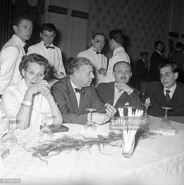Italian writers Eugenio Montale Guido Piovene and Enzo Bettiza and Italian writer and Eugenio Montale's wife Drusilla Tanzi sitting at the table at...