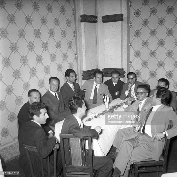 Italian writers Giorgio Bassani and Italo Calvino sitting at the table with some other writers at the Incontri Letterari former San Pellegrino Awards...