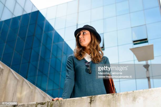Italian young business woman wearing a cap in a business center building